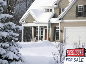 A homeowner is selling their home in the winter. House covered in snow with a for sale and foreclosure sign in front of the house.